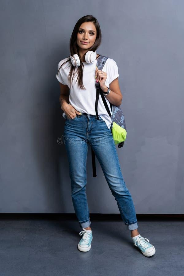 Full längdstående av den unga härliga kvinnan Le studentflickan som går på ett lopp Isolerat p? gr? bakgrund arkivbild
