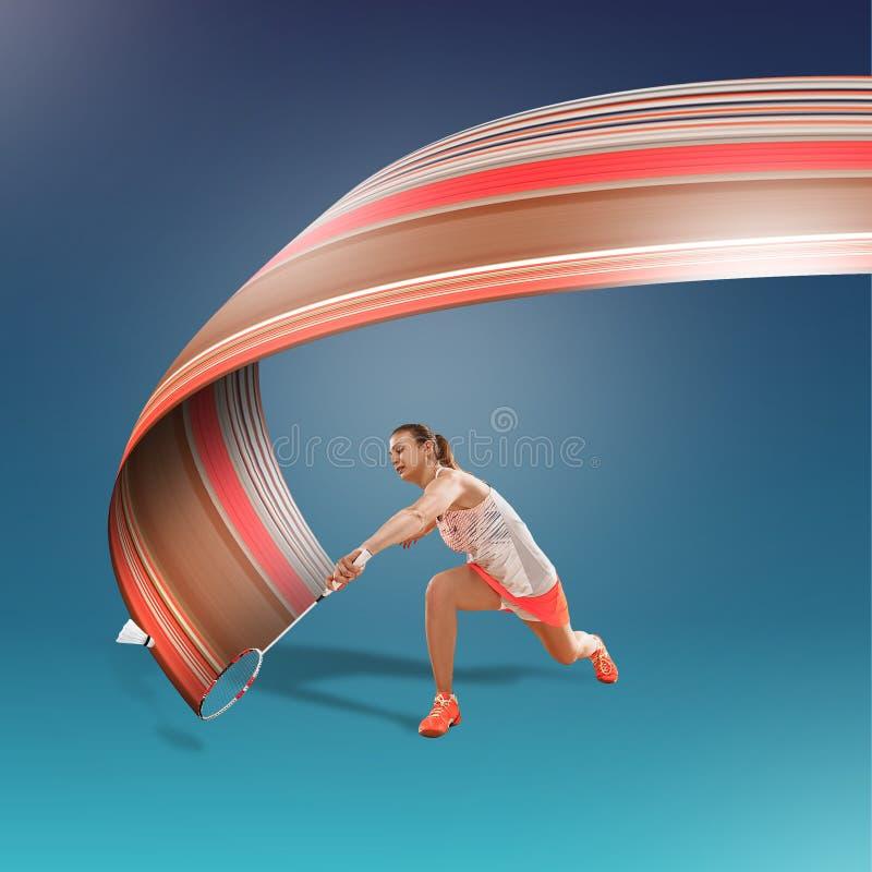 Full längdstående av den unga kvinnan som spelar badminton som isoleras på blå bakgrund arkivbild