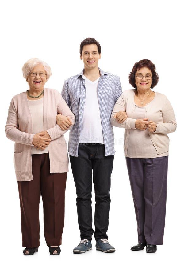 Full längdstående av den unga mannen med två äldre kvinnor royaltyfri fotografi