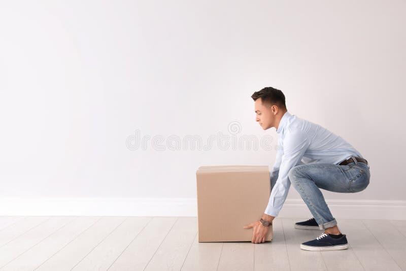 Full längdstående av den unga mannen som lyfter den tunga kartongen nära den vita väggen royaltyfri bild