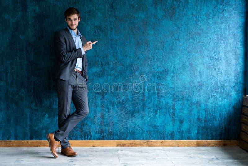Full längdstående av den unga stiliga affärsmannen med leende som pekar med fingret arkivfoto