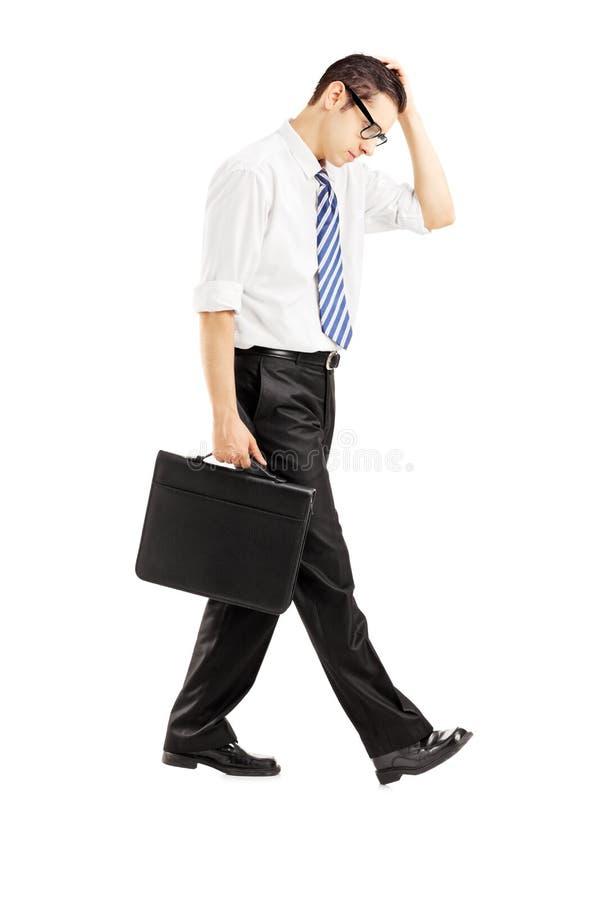 Full längdstående av en besviken affärsman som går med arkivbild