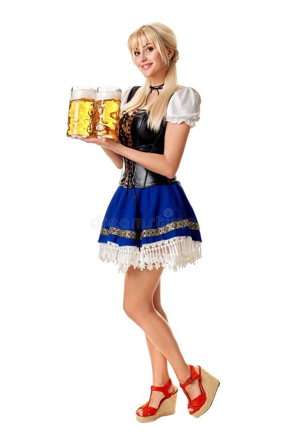 Full längdstående av en blond kvinna med hållande ölexponeringsglas för traditionell dräkt som isoleras på vit bakgrund arkivfoto
