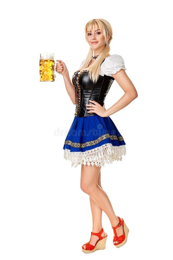 Full längdstående av en blond kvinna med hållande ölexponeringsglas för traditionell dräkt som isoleras på vit bakgrund royaltyfri foto