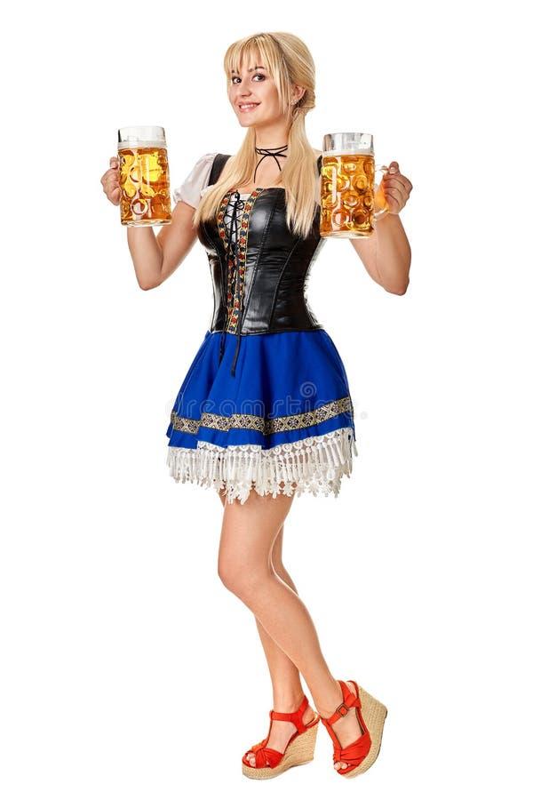 Full längdstående av en blond kvinna med hållande ölexponeringsglas för traditionell dräkt som isoleras på vit bakgrund fotografering för bildbyråer