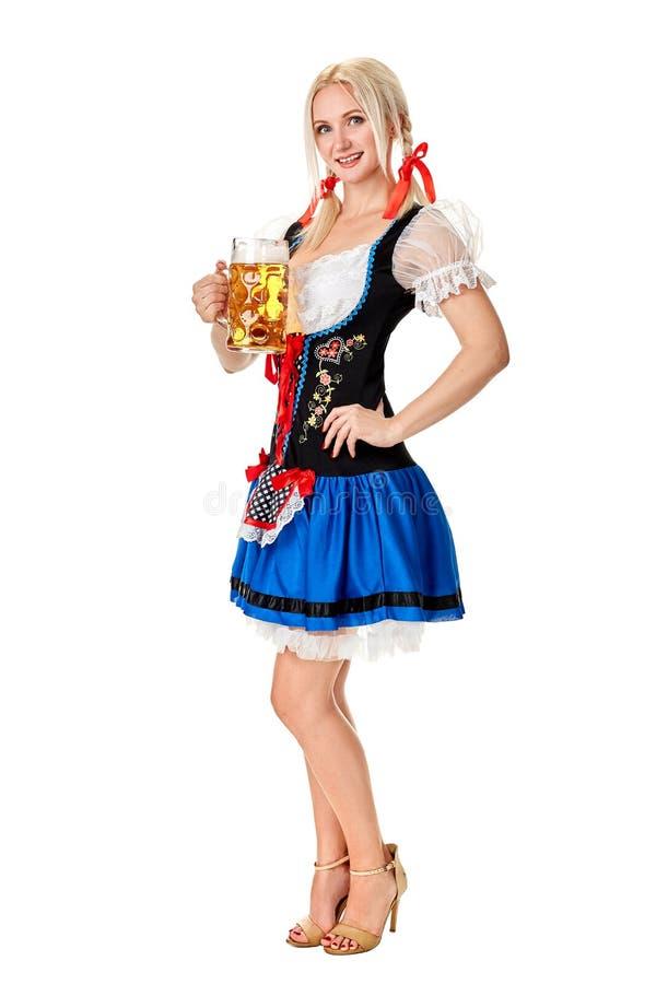 Full längdstående av en blond kvinna med hållande ölexponeringsglas för traditionell dräkt som isoleras på vit bakgrund royaltyfria foton