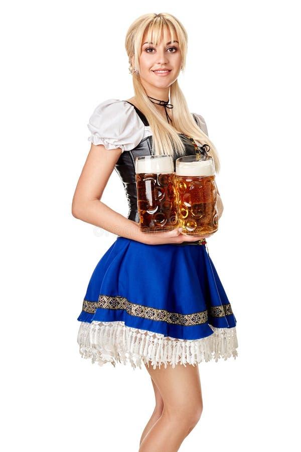 Full längdstående av en blond kvinna med hållande ölexponeringsglas för traditionell dräkt som isoleras på vit bakgrund royaltyfri bild