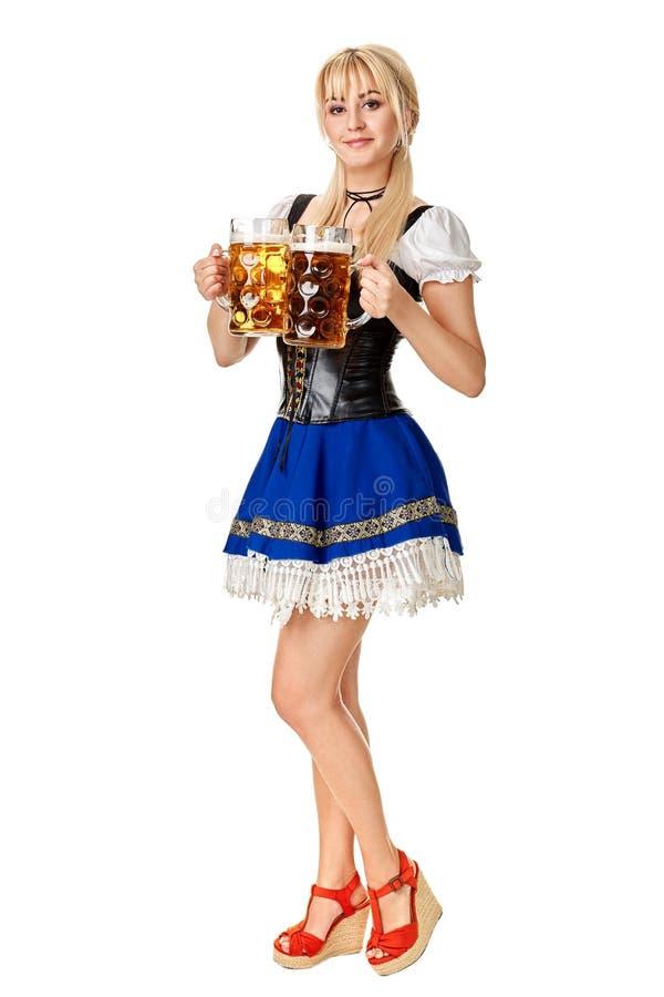Full längdstående av en blond kvinna med hållande ölexponeringsglas för traditionell dräkt som isoleras på vit bakgrund arkivfoton