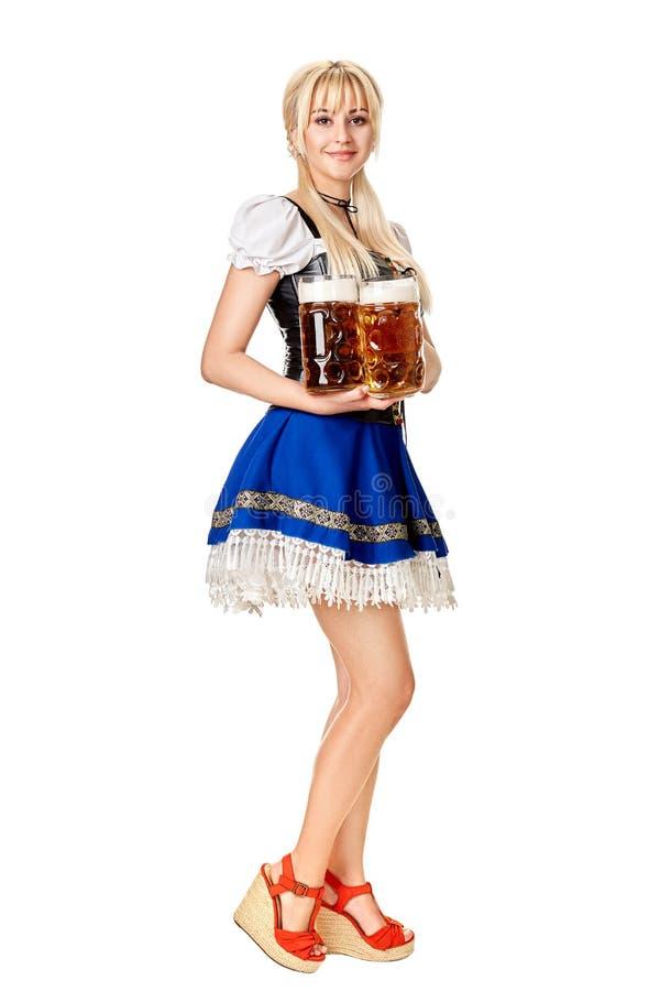 Full längdstående av en blond kvinna med hållande ölexponeringsglas för traditionell dräkt som isoleras på vit bakgrund royaltyfri fotografi