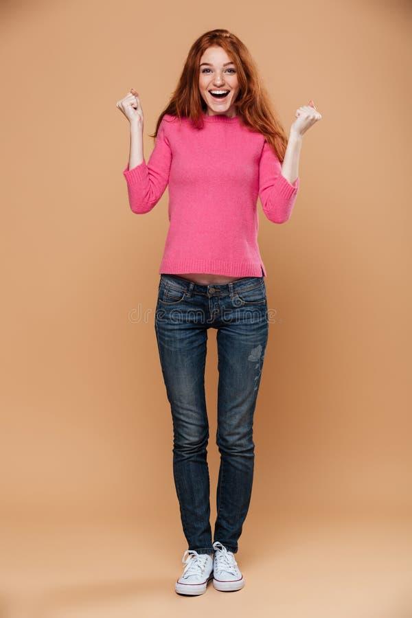 Full längdstående av en glad ung rödhårig manflicka arkivfoton