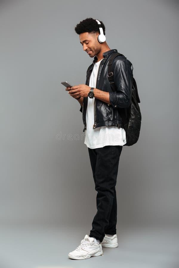 Full längdstående av en gladlynt ung afro amerikansk man royaltyfri bild