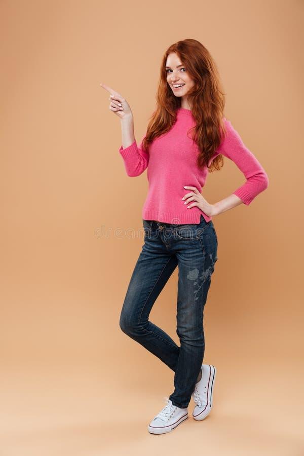 Full längdstående av en gladlynt ung rödhårig manflicka royaltyfria foton