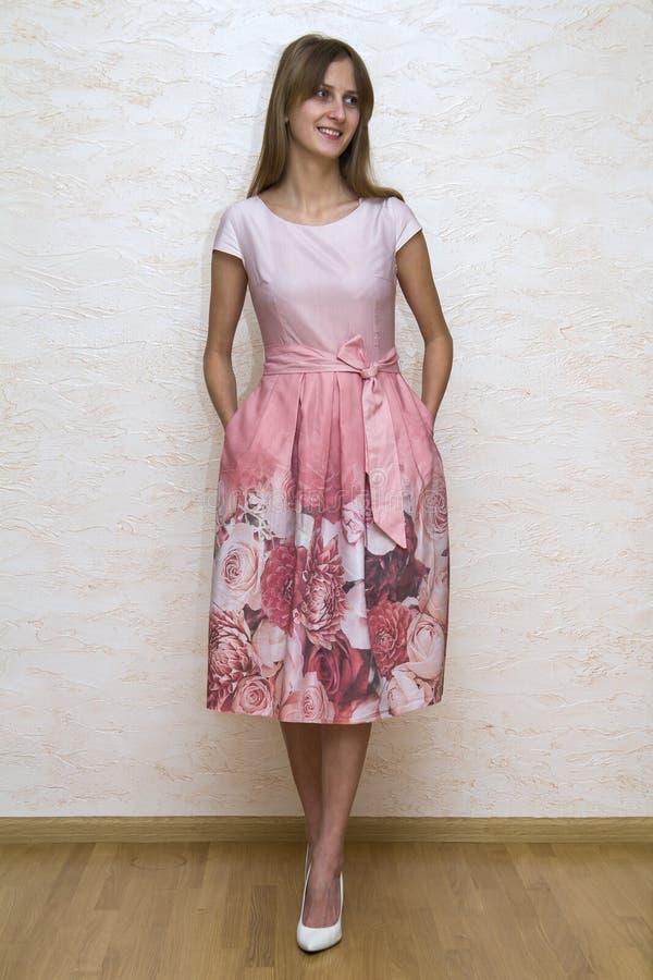 Full längdstående av en härlig ung lycklig säker flicka med långt blont hår som poserar i sommarklänning med rosa blom- design royaltyfria foton