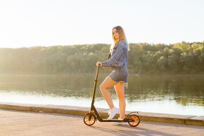 Full längdstående av en kvinna som rider en sparkcykel royaltyfria bilder