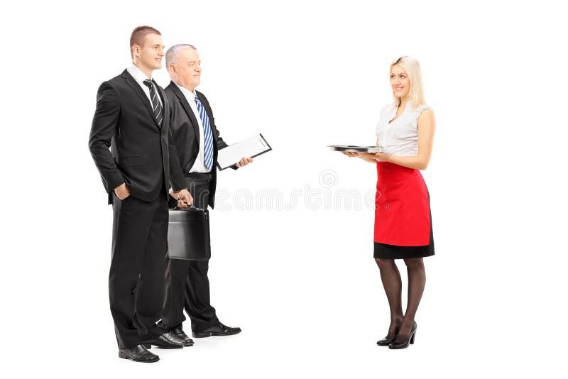 Full längdstående av en le blond servitris med magasinservi royaltyfria bilder