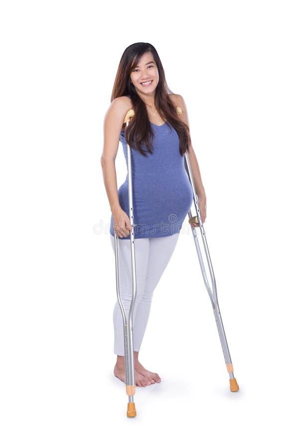 Full längdstående av en le gravid kvinna som använder kryckan royaltyfria bilder