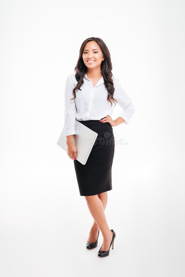 Full längdstående av en le hållande bärbar dator för asiatisk affärskvinna royaltyfri bild