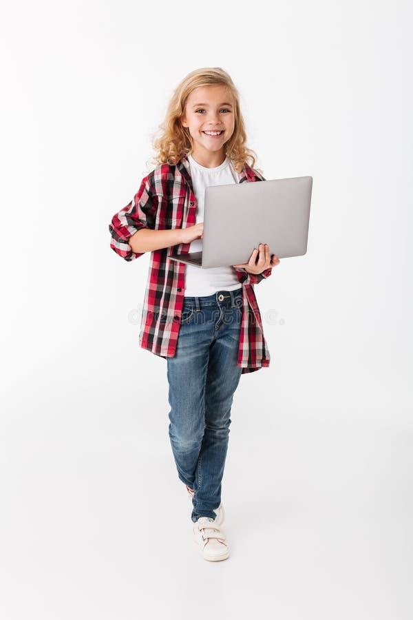 Full längdstående av en le hållande bärbar dator för liten flicka fotografering för bildbyråer