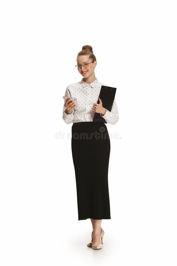 Full längdstående av en le lärarinna som rymmer en mapp isolerad mot vit bakgrund royaltyfri fotografi