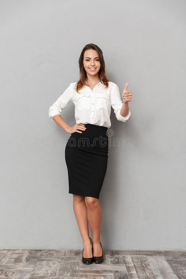 Full längdstående av en le ung affärskvinna royaltyfria foton