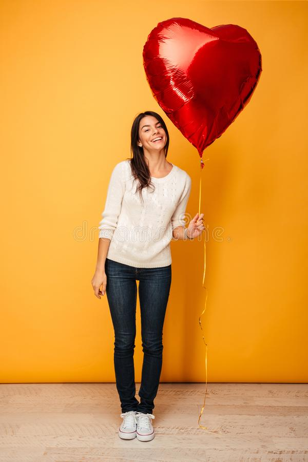 Full längdstående av en le ung kvinna arkivfoto