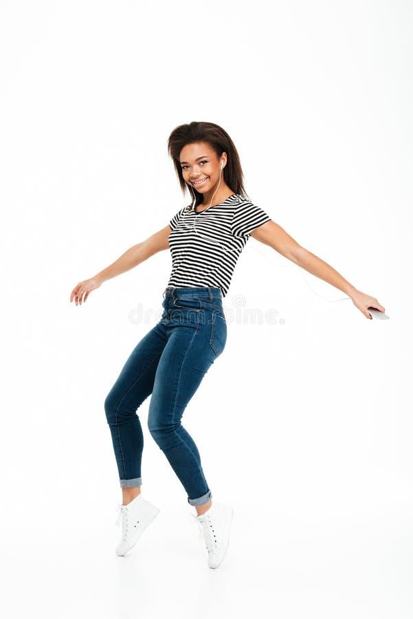 Full längdstående av en lycklig bekymmerslös afrikansk flickabanhoppning royaltyfria bilder