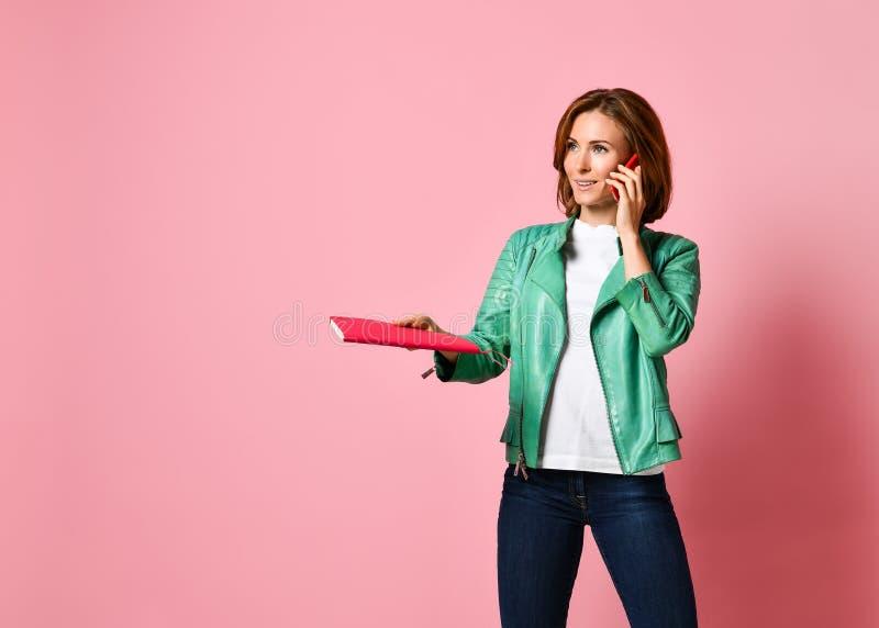 Full längdstående av en lycklig ung kvinna som talar på telefonen arkivbild