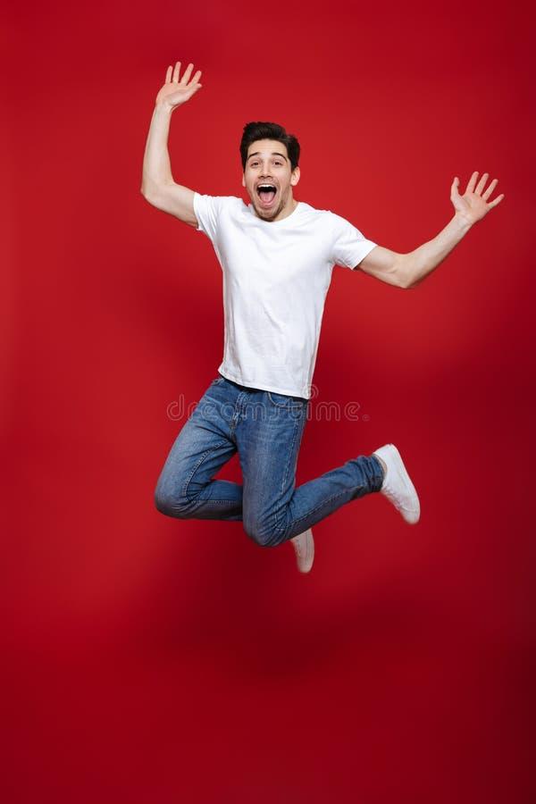 Full längdstående av en lycklig ung man i den vita t-skjortan royaltyfri foto
