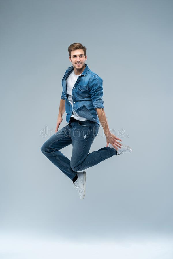 Full längdstående av en lycklig upphetsad beardedman som hoppar och ser kameran som isoleras över grå bakgrund arkivfoto