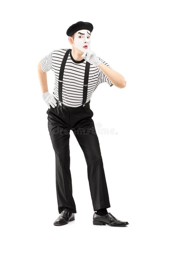 Full längdstående av en manlig farskonstnär som gör en gest tystnad arkivfoto