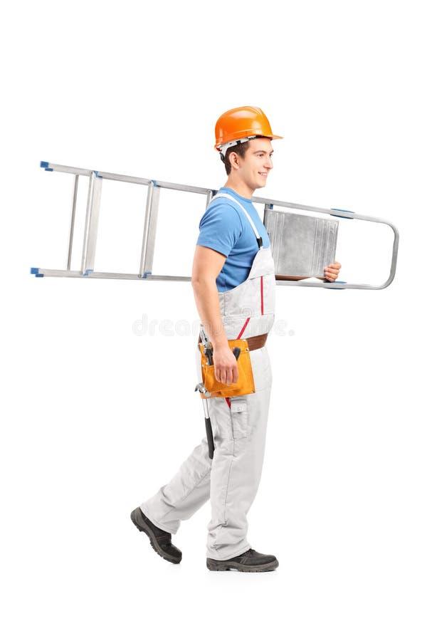 Full längdstående av en repairman med en hjälm som bär en knatte fotografering för bildbyråer