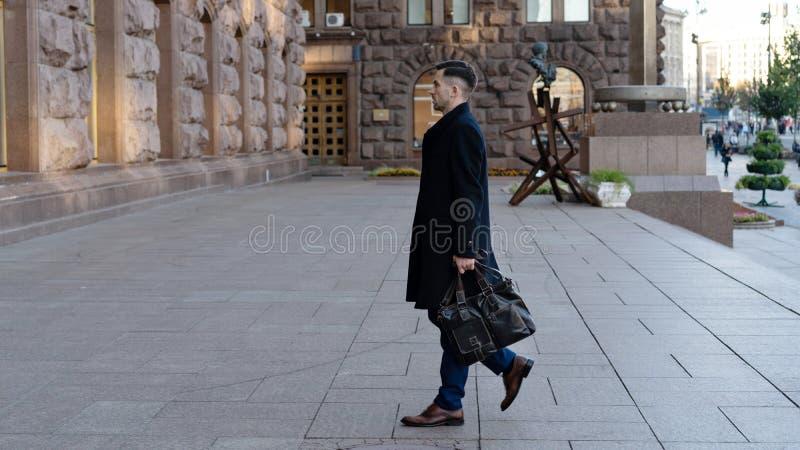 Full längdstående av en säker ung affärsman som går i staden med en påse arkivfoton