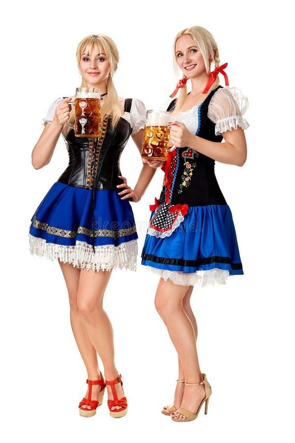 Full längdstående av en två blond kvinna med hållande ölexponeringsglas för traditionell dräkt som isoleras på vit bakgrund royaltyfria bilder