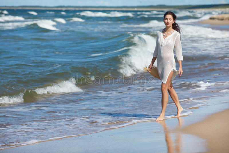 Full längdstående av en ung kvinna i kortslutningar som går på bet royaltyfria bilder