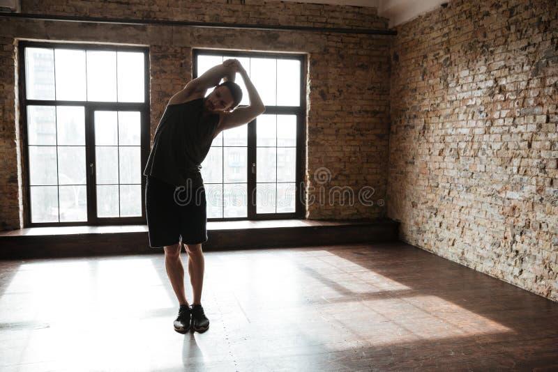 Full längdstående av en ung sund idrottsman nenmansträckning arkivbild