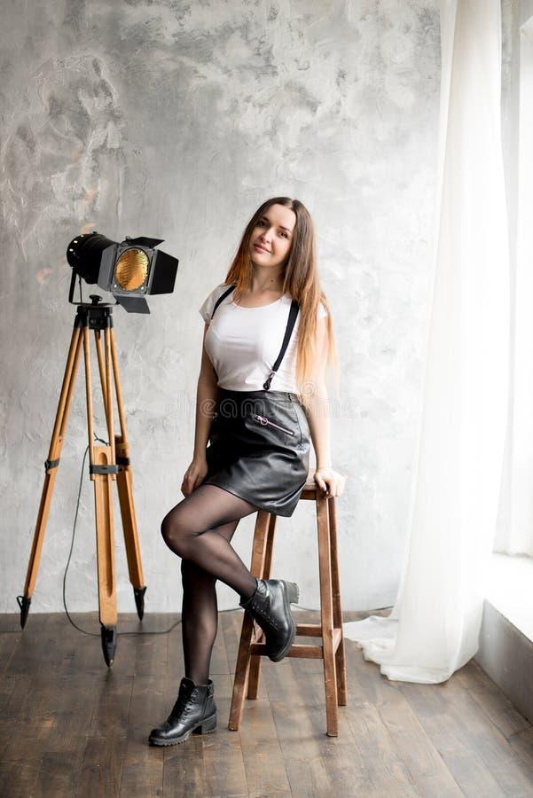 Full längdstående av ett le sammanträde för ung kvinna på stol arkivfoton