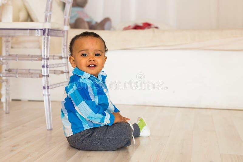 Full längdstående av ett ungt pojkesammanträde för blandat lopp på golvet royaltyfria foton