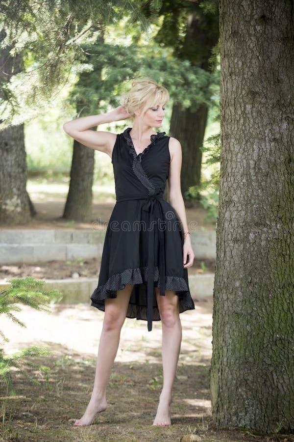 Full längdstående av härliga barfota unga kvinnor som bär den svarta klänningen, medan stå under sörja trädet arkivbild