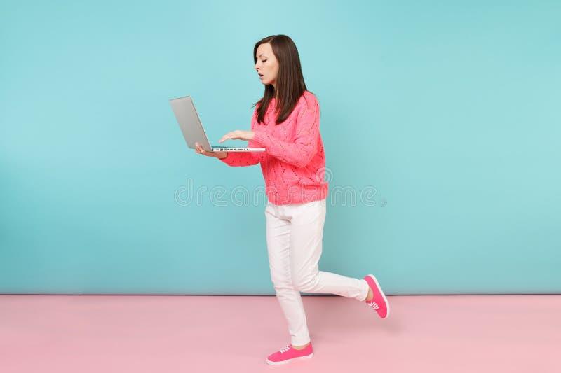 Full längdstående av kvinnan i den stack rosa tröjan, vita flåsanden genom att använda bärbar datorPCdatoren som isoleras på ljus arkivfoto