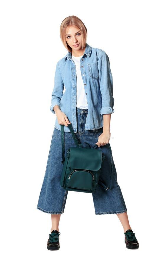 Full längdstående av kvinnan i stilfulla skor som rymmer ryggsäcken royaltyfria foton