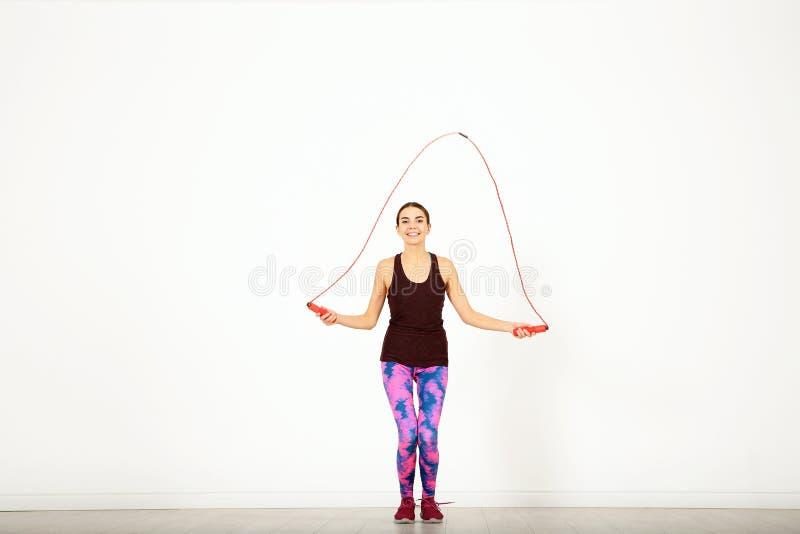 Full längdstående av ung sportive kvinnautbildning med hopprepet i rum royaltyfri fotografi