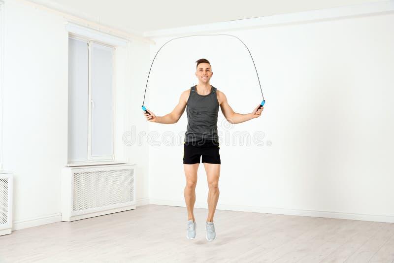 Full längdstående av ung sportive manutbildning med hopprepet i rum royaltyfri fotografi