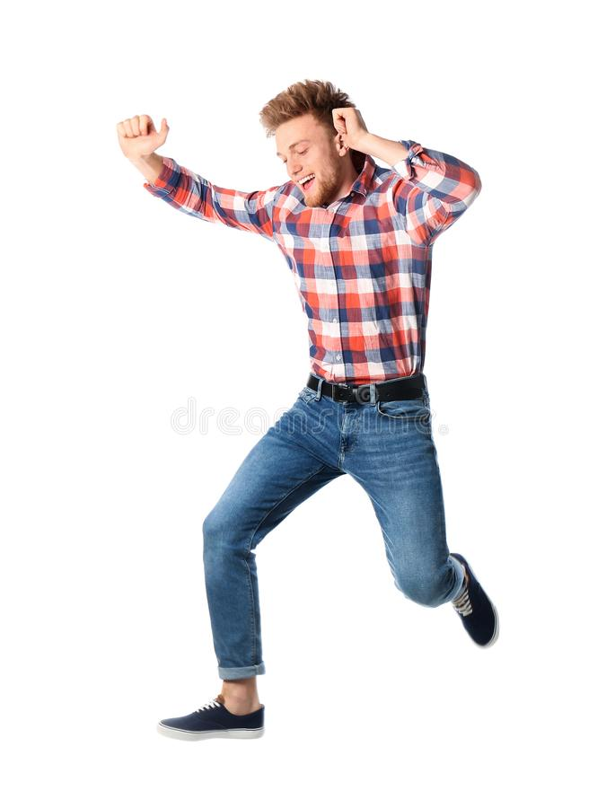 Full l?ngdst?ende av den lyckliga stiliga mannen som hoppar p? vit royaltyfri fotografi