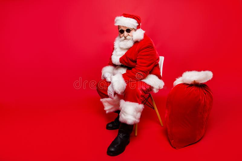 Full legs body size half turn aged mature stylish trendy good-lo. Oking Saint Nicholas in shoes headwear with white beard look on camera sit in chair isolated on stock images