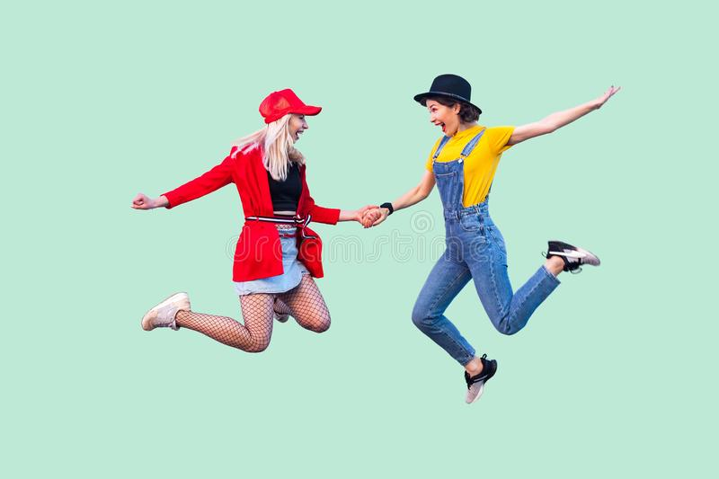 Full legs body size portrait of two happy screaming stylish hipster girls in fashionable clothes are jumping up in the air and. Celebrated a win. Indoor studio royalty free stock image
