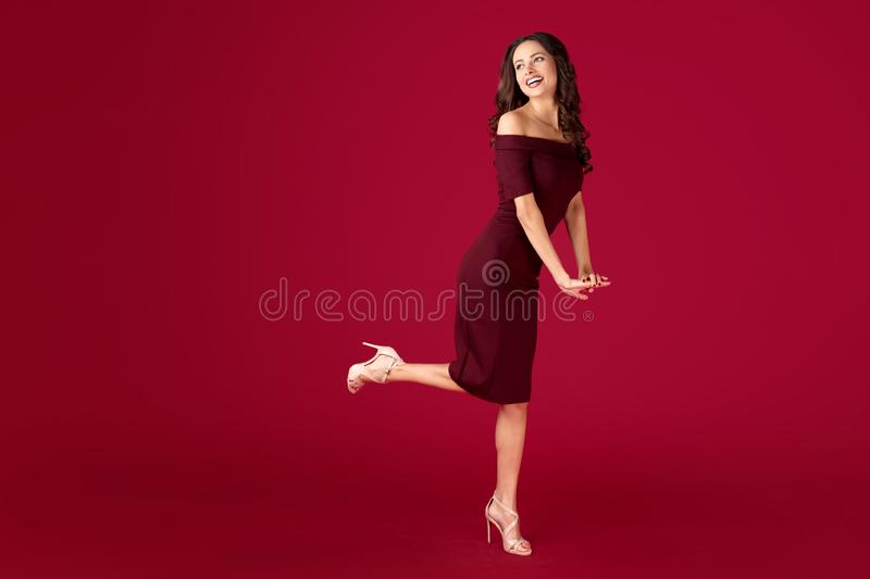 Full lengh portrait of elegant young woman in maroon dress over red background. Full lengh portrait of elegant young woman in maroon dress over red background stock photos