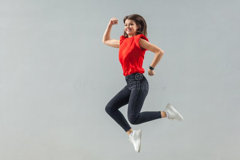 Full lenght of happy beautiful brunette young woman in casual red shirt jumping up, toothy smile and looking at camera with royalty free stock image