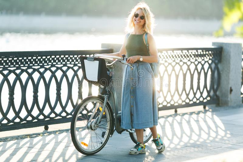Full-lenght photo of curly blonde girl looking at side in denim skirt standing next to bike on bridge in city stock photography