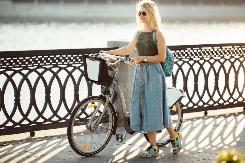 Full-lenght photo of curly blonde woman looking at side in denim skirt standing next to bike on bridge in city royalty free stock image