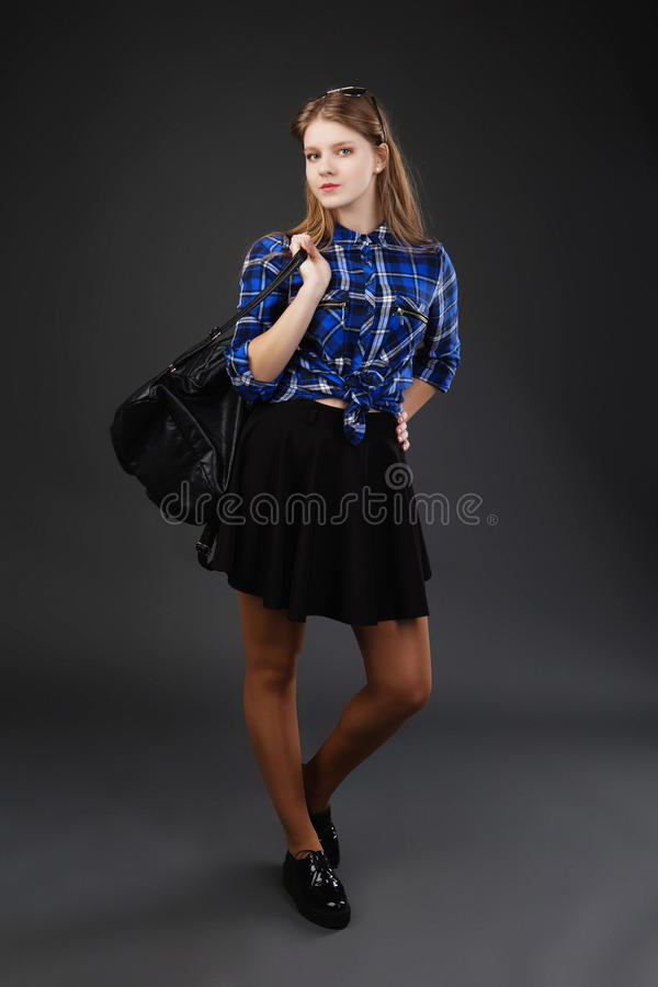 Full-lenght portrait of a girl in a plaid shirt and black skirt stock image